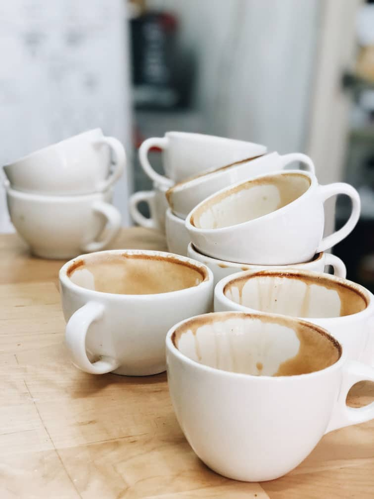 piled dirty coffee mugs do the dishes to keep your house clean