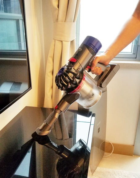 person holding dyson vacuum with duster nozzle