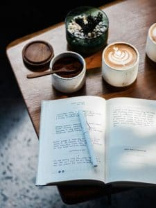 coffeetable with cup of coffee and journal open on a page how to use a planner