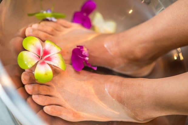 feet in footbath with flowers at home spa
