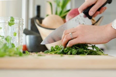 sideview of someone chopping parsley