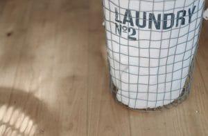 laundry hamper in bedroom to declutter the bedroom