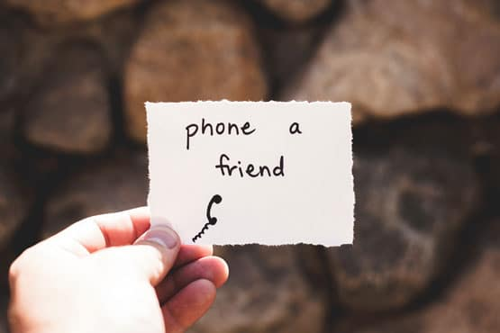 hand holding a piece of paper that says phone a friend stay connected to deal with stress and anxiety
