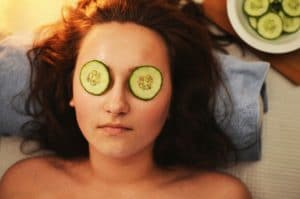 woman laid down with cucumber slices on her eyes