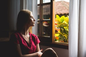 woman sitting in front of window meditating